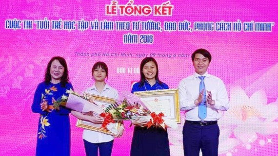 Thứ trưởng Bộ Giáo dục và Đào tạo Nguyễn Thị Nghĩa (trái) và Bí thư Trung ương Đoàn Nguyễn Ngọc Lương (phải) trao giải Nhất cuộc thi cho thí sinh. Ảnh: Thu Hoài - TTXVN