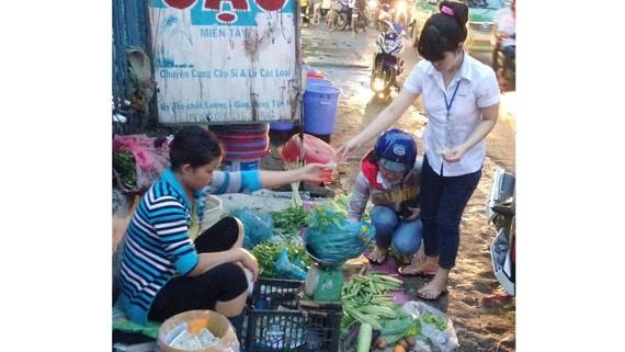Công nhân tan ca chọn mua rau tại chợ tự phát         trên đường Lê Văn Chí, quận Thủ Đức.  Ảnh: HẢI THU