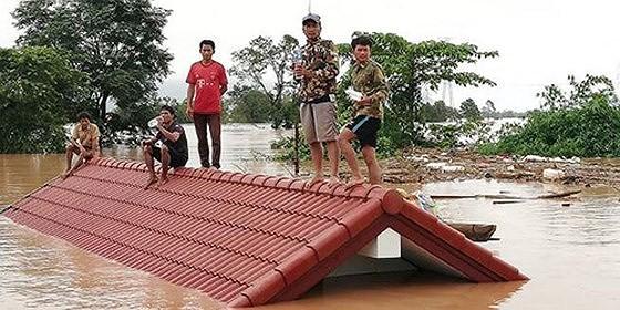 Người dân đứng trên nóc nhà chờ giải cứu khi nước lũ dâng cao do vỡ đập