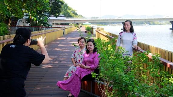 Chưa nghiệm thu nhưng đường đi bộ làm bằng gỗ lim bên sông Hương đã thu hút đông du khách đến vãn cảnh