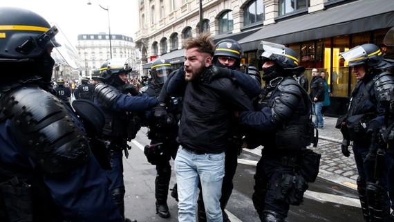 Một người biểu tình bị bắt gần ga xe lửa Saint Lazare ở Paris ngày 8-12-2018. REUTERS