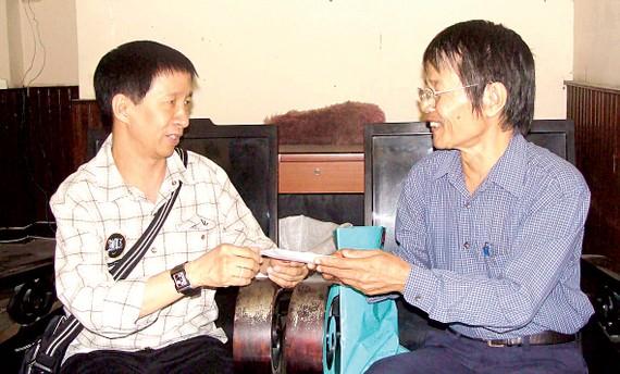 Nhà thơ Lâm Xuân Thi (trái) trao 10 triệu đồng của Quỹ Tình thơ cho nhà thơ Hà Nguyên Dũng