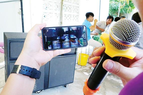Một đám tiệc, chỉ cần dàn loa, micro kết nối phần mềm karaoke trên điện thoại di động, là đủ hành hạ làng xóm                     .  Ảnh: DŨNG PHƯƠNG
