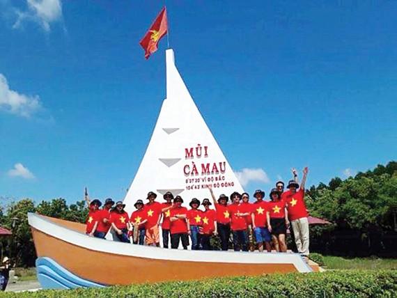 Du khách chụp ảnh lưu niệm tại biểu tượng Mũi Cà Mau Ảnh: M.K.