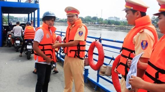 Cảnh sát giao thông đường thủy TPHCM hướng dẫn khách đi phà mặc áo phao để đảm bảo an toàn