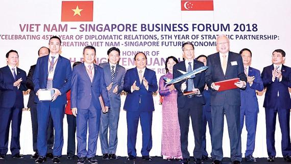 Thủ tướng Nguyễn Xuân Phúc  chứng kiến lễ trao các văn kiện hợp tác giữa hai nước tại diễn đàn. Ảnh: TTXVN