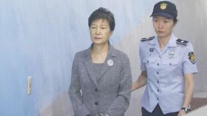 Cựu Tổng thống Hàn Quốc Park Geun-hye (trái) được áp giải tới Tòa án Quận trung tâm Seoul ngày 25-8-2017. Ảnh: THE STRAITS TIME