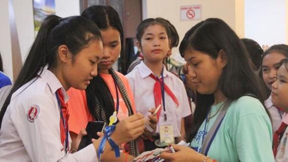 Thiếu nhi Việt Nam, Lào, Campuchia trao đổi thông tin liên lạc tại trại hè. Ảnh: TTXVN