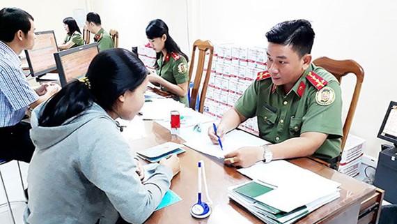 Cán bộ Phòng Quản lý xuất nhập cảnh hướng dẫn người dân và tiếp nhận hồ sơ làm hộ chiếu