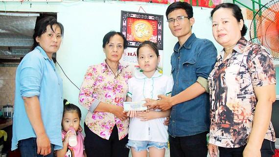 Đại diện Báo SGGP trao 25,5 triệu đồng do bạn đọc báo ủng hộ gia đình cháu Lê Thị Bảo Linh. Ảnh: NGỌC OAI