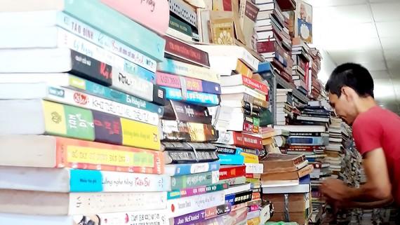Những chồng sách cao ngất, chất kín lối, nằm im lìm trong các quầy sách tại phố sách cũ Trần Nhân Tôn (quận 5)