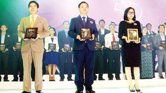 Ông Lê Viết Hải - Chủ tịch HĐQT, Tổng Giám đốc Công ty Cổ phần Tập đoàn  Xây dựng Hòa Bình (đứng giữa) nhận bảng vàng chứng nhận tại buổi lễ tôn vinh