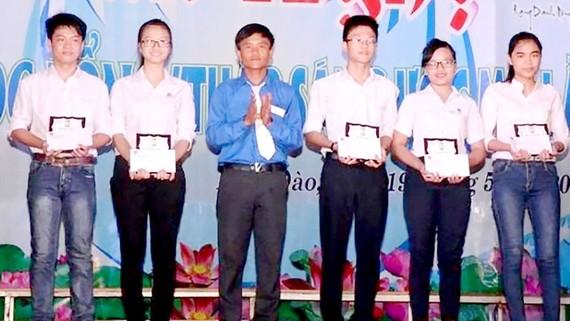 Trần Hữu Việt (thứ 3 từ trái sang) tặng học bổng cho học sinh nghèo của địa phương