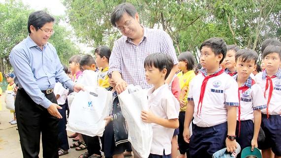 PGS-TS Trần Văn Ngọc (bìa trái) và bác sĩ Cao Xuân Minh tặng quà học sinh Trường Tiểu học Tân Hòa