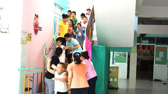 Cô giáo, bảo mẫu hướng dẫn trẻ thoát nạn trong buổi diễn tập