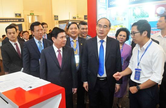 Bí thư Thành ủy Nguyễn Thiện Nhân và Chủ tịch UBND TP Nguyễn Thành Phong tham quan các gian hàng tại triển lãm diễn đàn. Ảnh: CAO THĂNG
