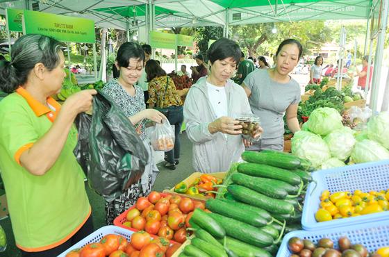 Người dân mua nông sản an toàn tại chợ phiên ở Công viên Lê Thị Riêng sáng 24-9-2017. Ảnh tư liệu: CAO THĂNG