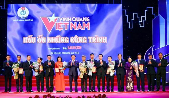 Phó Thủ tướng Vương Đình Huệ, Trưởng Ban Tuyên giáo Trung ương Võ Văn Thưởng, cùng lãnh đạo các bộ ngành với đại diện của 8 công trình tiêu biểu của đất nước. Ảnh: VGP