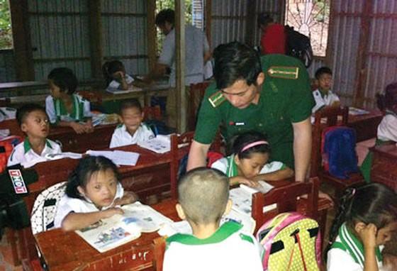 Thượng úy Trần Bình Phục đang hướng dẫn từng con chữ cho các cháu lớp học tình thương trên đảo Hòn Chuối(thị trấn Sông Đốc, huyện Trần Văn Thời, tỉnh Cà Mau).