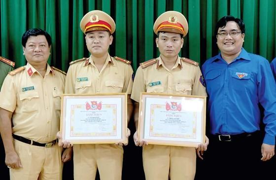 Đại diện Thành đoàn TNCS TPHCM đã trao bằng khen tuyên dương nghĩa cử đẹp của thượng úy Vũ Đình Nam và trung úy Đoàn Tấn Phú. Ảnh: THÁI PHƯƠNG