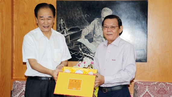Xinhua President Cai Mingzhao hands over presents to Sai Gon Giai Phong Newspaper. (Photo: Sggp)