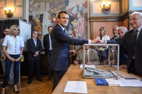 French President Emmanuel Macron (centre) casts his ballot next to his wife Brigitte Macron (left) at a polling station during the first round of the French legislative elections in Le Touquet, on June 11, 2017. — AFP/VNA
