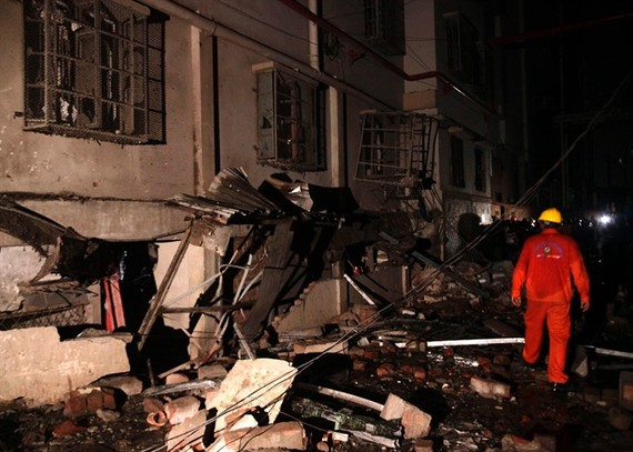 A Bangladeshi rescue worker walks through rubble and debris at a garment factory in Gazipur on Monday, after an explosion at the factory on the outskirts of Dhaka.
