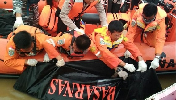 Members of a rescue team are retrieving a body from the Musi river in Palembang, South Sumatra province, after a boat carrying 55 people hit a large wave and sank amid bad weather. At least 13 people died. (Source: AFP)