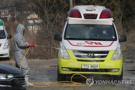 A quarantine official disinfects an ambulance in the vicinity of a layer chicken farm in the city of Pocheon, northeast of Seoul, on Jan. 4, 2018, where the quarantine authorities confirmed an outbreak of an avian influenza virus. (Yonhap)