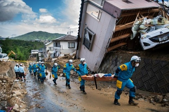 In one part of Kumano, Japan, the nose of a white car was just visible underneath the top floor of a home that had been torn from the rest of the building and swept down a hillside by floods. — AFP/VNA Photo