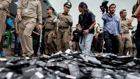 hai National Deputy Police Chief Wirachai Songmetta, centre with white gloves, law-enforcement officers and journalists walk past a pile of mobile batteries during a  recent raid in Bangkok. (Photo: AP)
