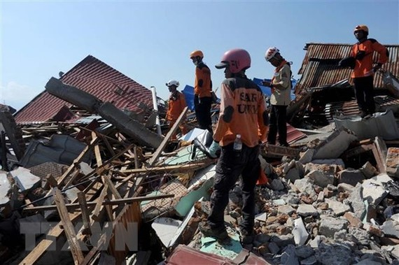 Search and rescue team members look for survivors in Palu, Central Sulawesi, Indonesia. (Photo: Xinhua/VNA)