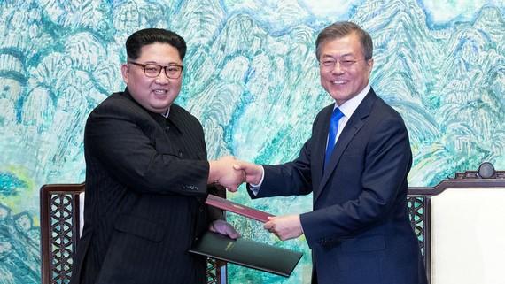 Chủ tịch Kim Jong Un và Tổng thống Moon Jae In ký văn bản sau hội đàm ngày 27-4. Ảnh: REUTERS