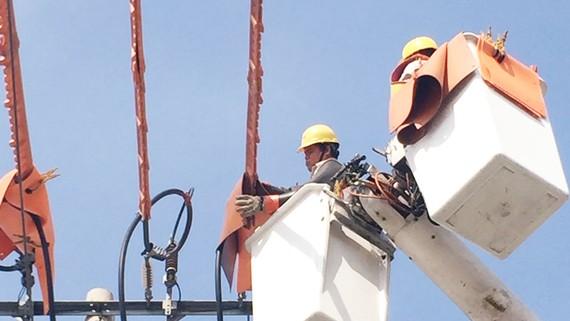 Công nhân EVNHCMC thi công trên đường dây đang mang điện (live-line)