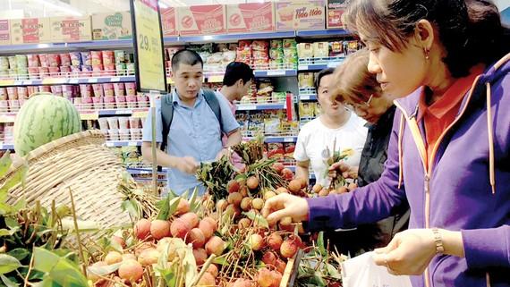 Người tiêu dùng lựa chọn trái vải trong siêu thị Co.opmart