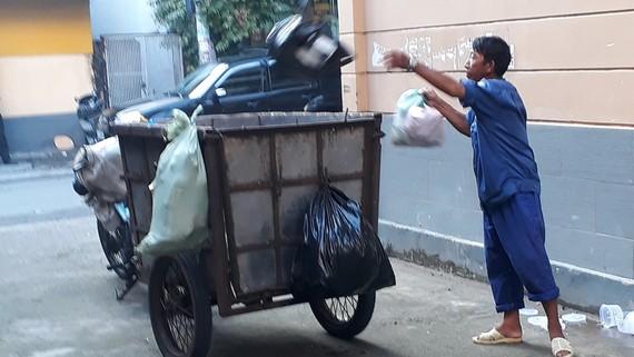 Người thu gom rác dân lập không trang bị bảo hộ lao động với chiếc xe lấy rác rất lạc hậu
