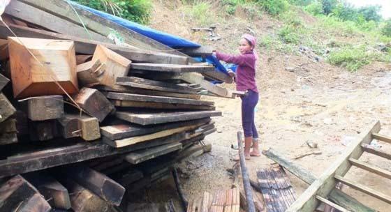 Chị Giàng Thị Dúa (tỉnh Điện Biên) thu gom những vật dụng còn lại sau khi ngôi nhà của chị bị mưa lũ làm đổ sập