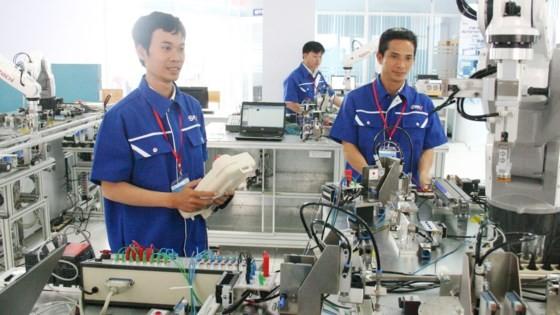 Robot sẽ thay thế nhiều phần việc của lao động trình độ thấp trong CMCN 4.0  (Trong ảnh: Kỹ sư Trung tâm Đào tạo Khu Công nghệ cao TPHCM làm việc với sự hỗ trợ của robot)