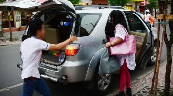 Khách sử dụng xe Uber tại TP.HCM - Ảnh: T.T.D.