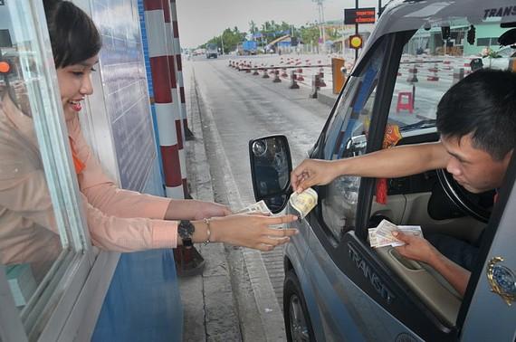Nhân viên thu phí vẫn phải giữ thái độ hòa nhã mặc dù tài xế đưa những cọc tiền lẻ khi đến trạm Cai Lậy - Ảnh: THANH TÚ