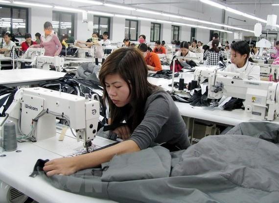 Công nhân sản xuất đồ may mặc. (Ảnh: Phạm Kiên/TTXVN)
