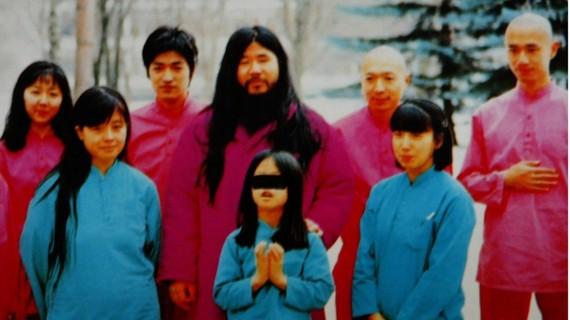 Shoko Asahara (áo hồng giữa ảnh) với vợ Tomoko và 2 con  gái (áo xanh, hàng đầu) cùng  nhóm các môn đệ. Ảnh: HO / EPA