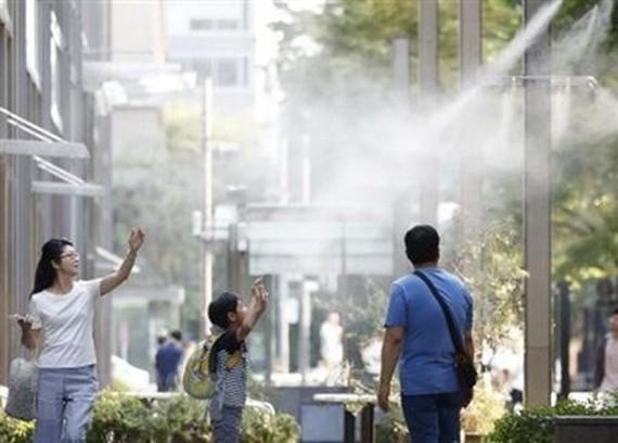 Người dân giải nhiệt tại các vòi phun nước ở Tokyo. (Nguồn: Kyodo/TTXVN)