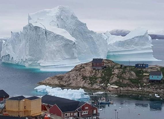 Tảng băng khổng lồ trôi sát với ngôi làng nhỏ tại Greenland, Đan Mạch. Ảnh: TheGuardian