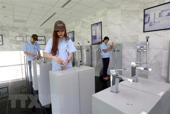 Kiểm tra các sản phẩm tại Công Ty TNHH Lixil Việt Nam, vốn đầu tư của Nhật Bản tại Quảng Nam. (Ảnh: Danh Lam/TTXVN)