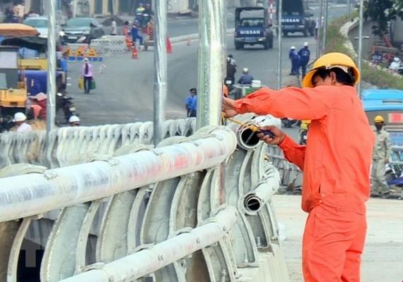 Công nhân đang gấp rút thi công giai đoạn cuối cầu vượt nút giao An Dương. (Ảnh: Nguyễn Văn Cảnh/TTXVN)