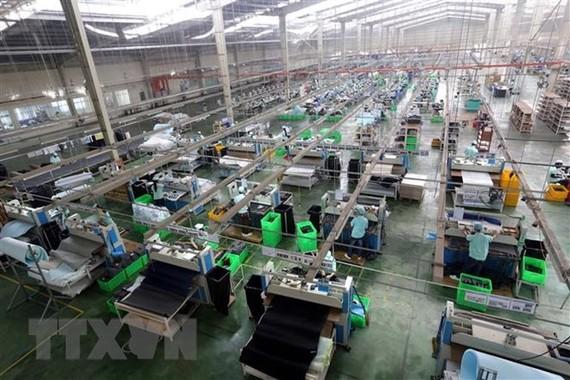 Dây chuyền sản xuất giày, dép xuất khẩu tại Công ty TNHH Midori Safety Footwear Việt Nam, vốn đầu tư của Nhật Bản tại khu công nghiệp Điện Nam-Điện Ngọc (Quảng Nam). (Ảnh: Danh Lam/TTXVN)