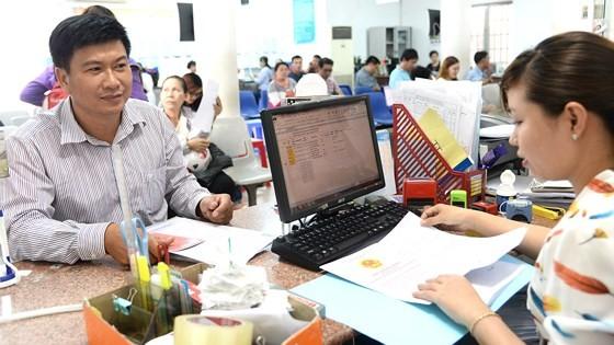 Người dân làm thủ tục hành chính tại bộ phận một cửa UBND huyện Hóc Môn. Ảnh: QUANG HUY