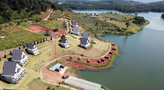 Dãy nhà gỗ dựng sát mép nước, xâm phạm vùng bảo vệ I của Di tích thắng cảnh quốc gia hồ Tuyền Lâm. (Ảnh: Đặng Tuấn/TTXVN)