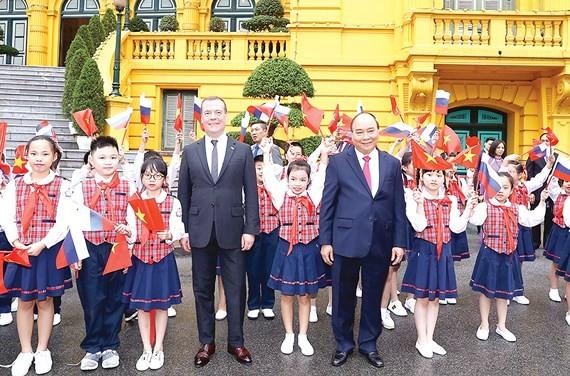 Thủ tướng Nguyễn Xuân Phúc và Thủ tướng Liên bang Nga Dmitry Medvedev chụp ảnh chung với thiếu nhi Hà Nội tại lễ đón. Ảnh: TTXVN